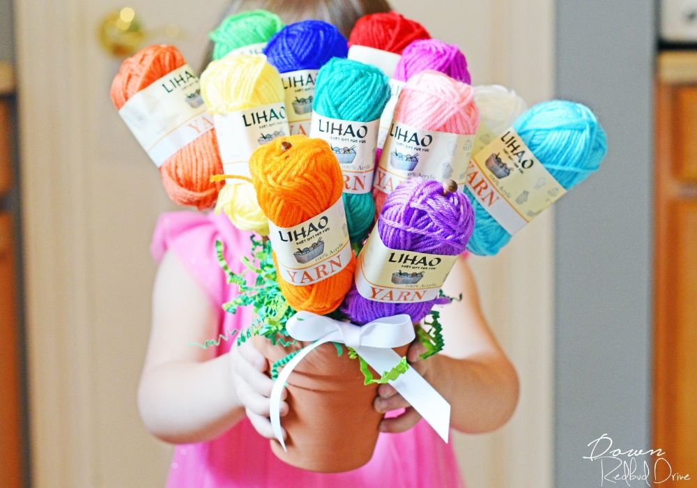little girl holding a yarn bouquet