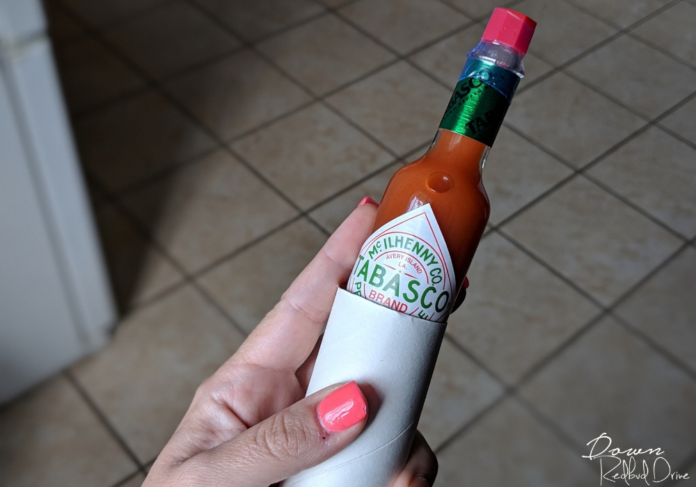small bottle of hot sauce fitting inside a paper towel tube