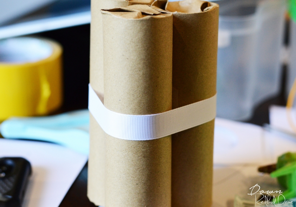 white ribbon wrapped around three brown paper tubes
