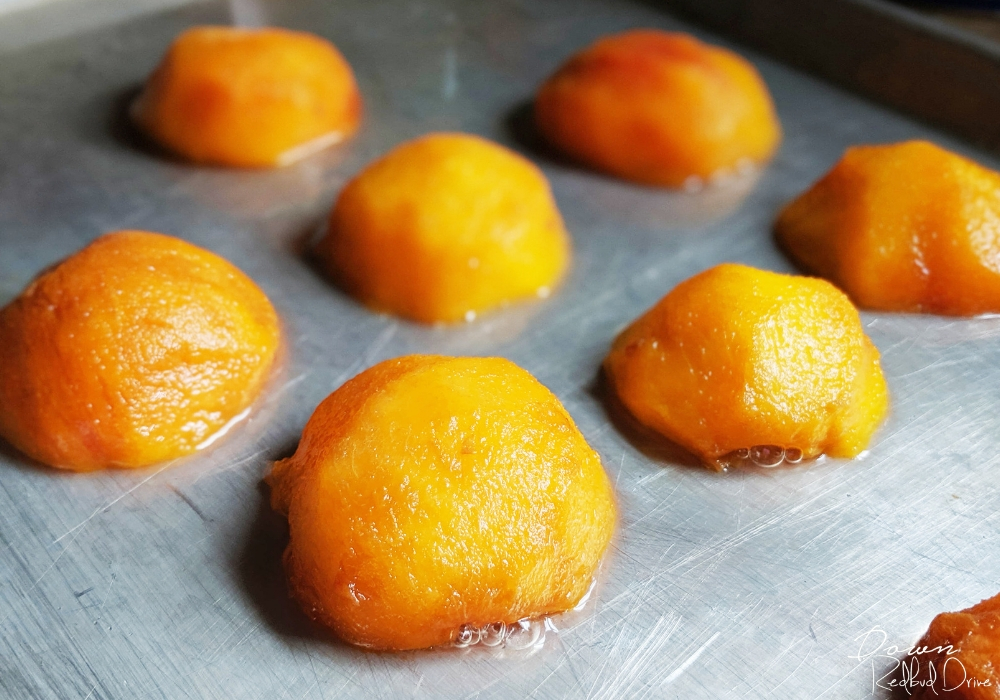 fresh peach halves on a silver baking sheet