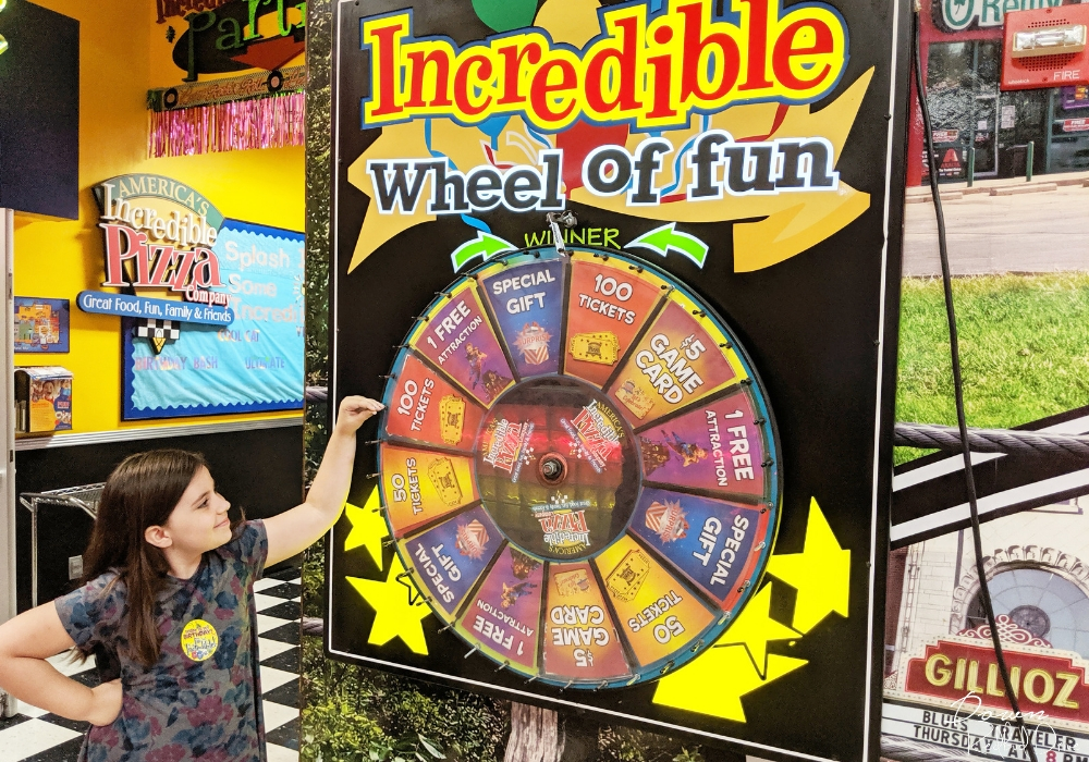 girl spinning the Incredible Wheel of Fun at Incredible Pizza