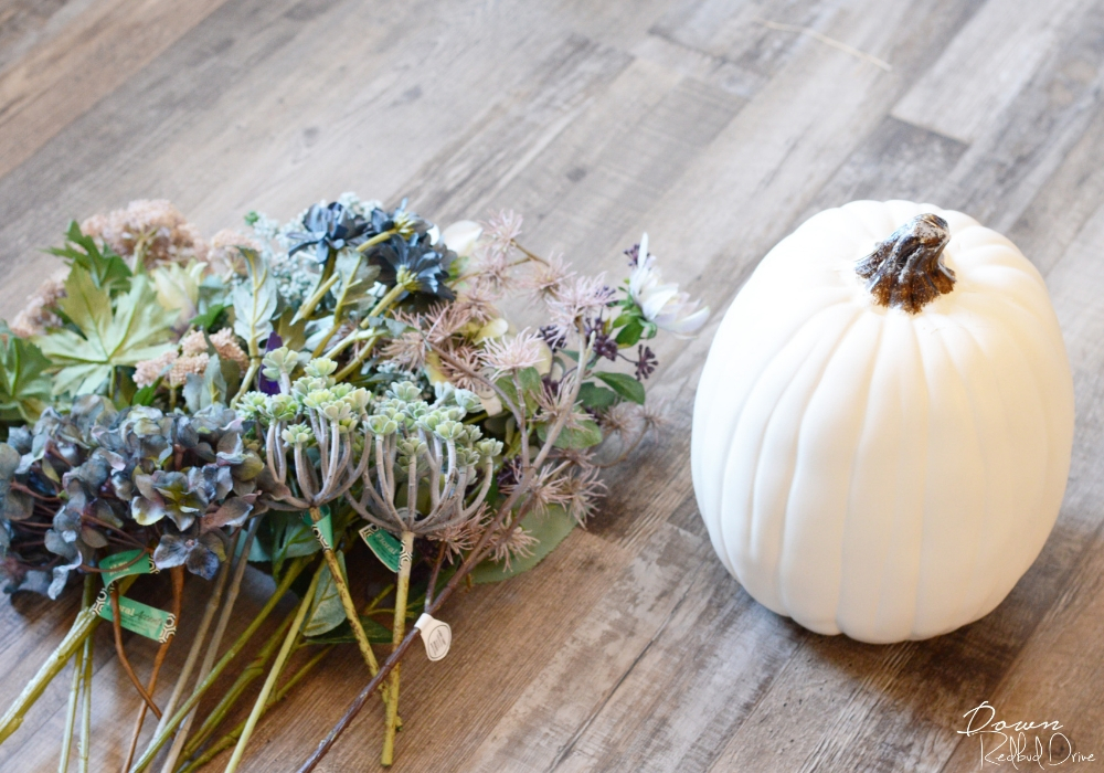 fake floral with a white pumpkin on a wooden floor