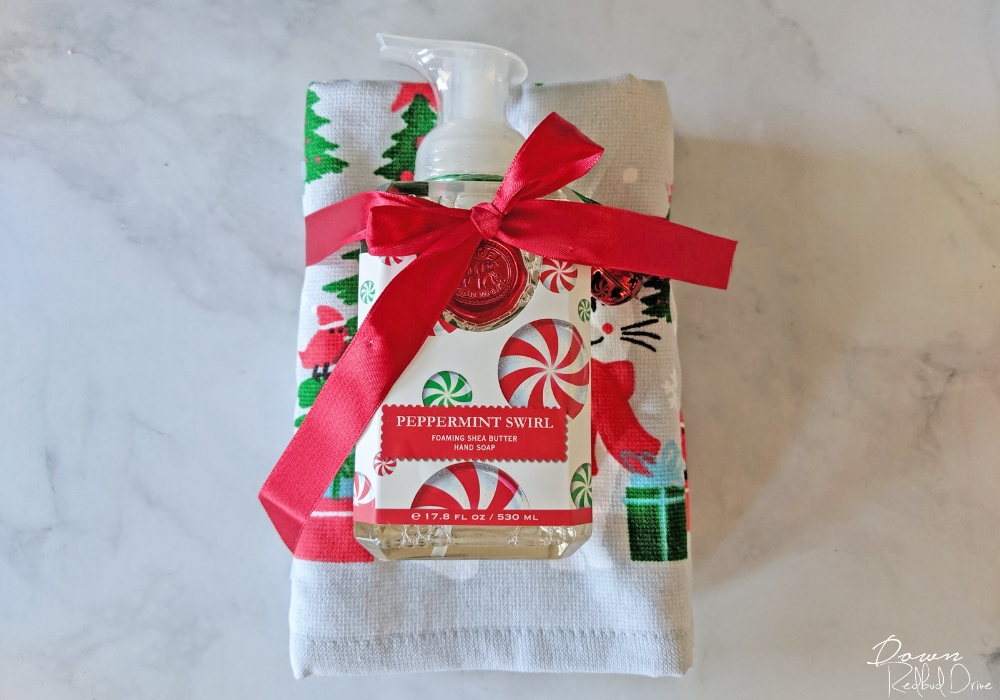 christmas kitchen towel and hand soap tied in a red ribbon