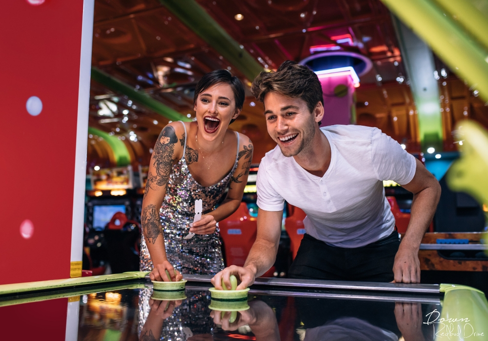 couple playing air hockey at an arcade