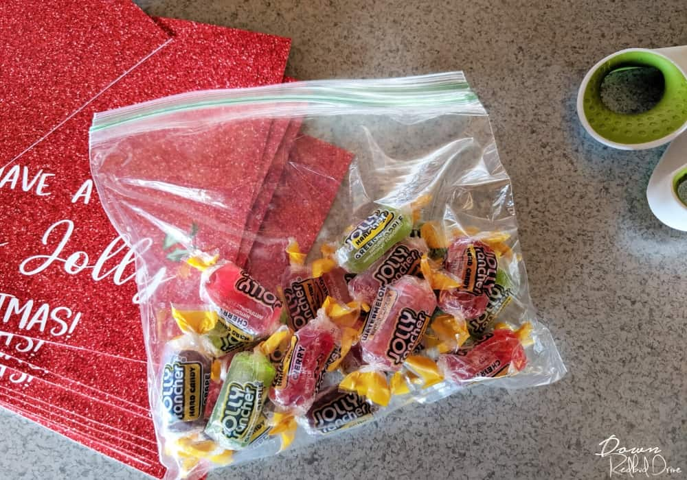 Bag of Jolly Ranchers next to Holly Jolly Christmas printable tags