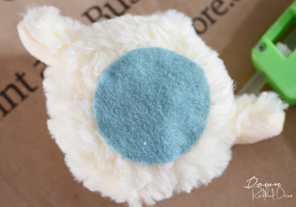a blue felt circle on the bottom of a stuffed lamb's head