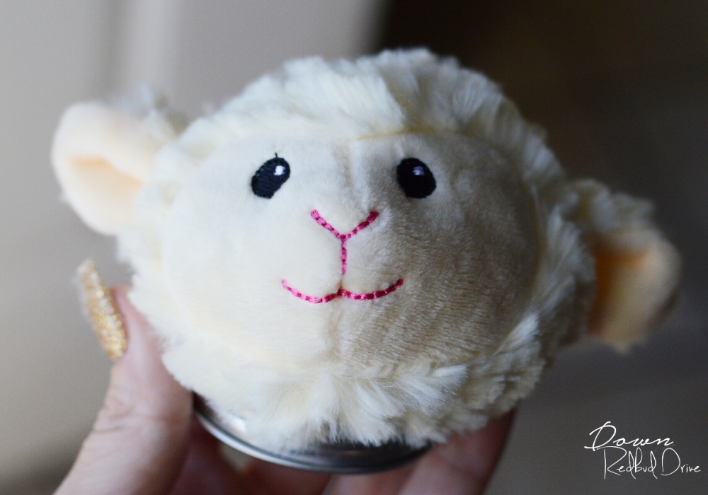a stuffed lamb's head attached to a jar lid