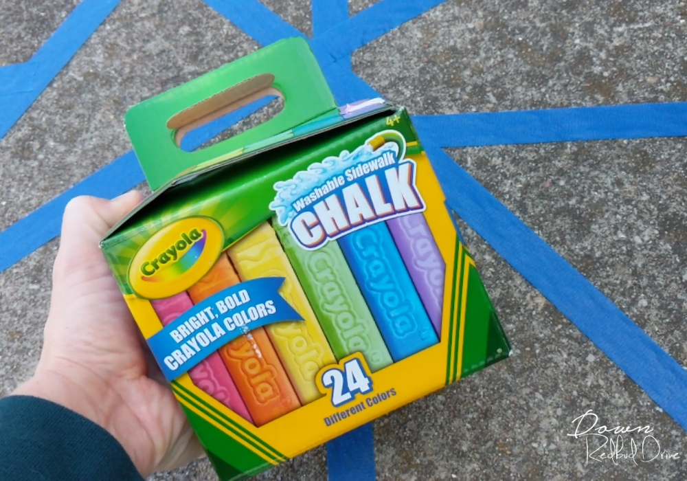 crayola sidewalk chalk with blue painter's tape on the concrete sidewalk behind it