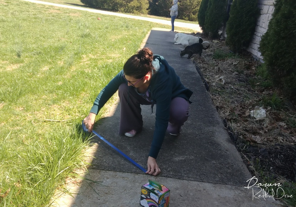 woman putting a strip of painter's tape on a sidewalk outside on a sunny day