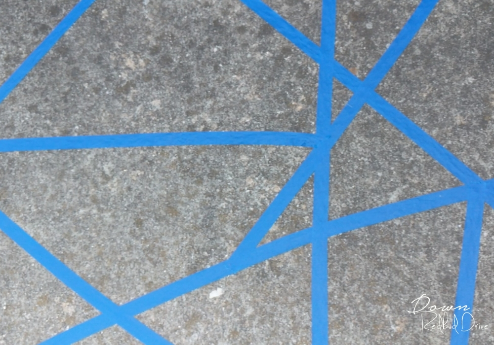 geomatric shapes made from blue painter's tape on a sidewalk