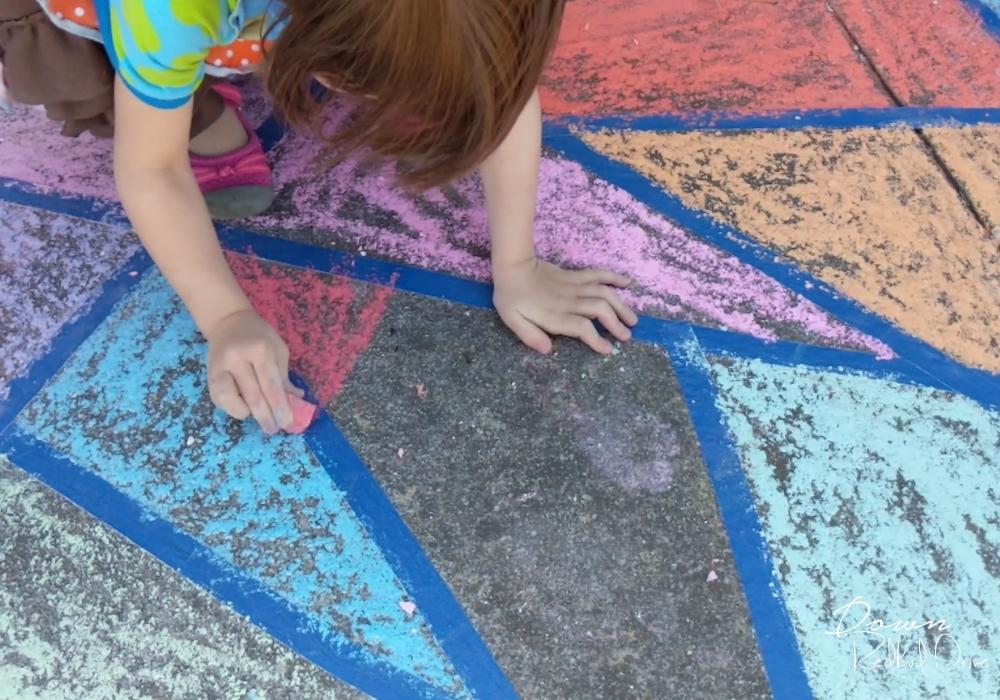 girl coloring a sidewalk chalk mosaic