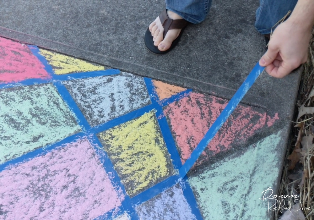 pulling blue painter's tape off a sidewalk that's been colored with sidewalk chalk