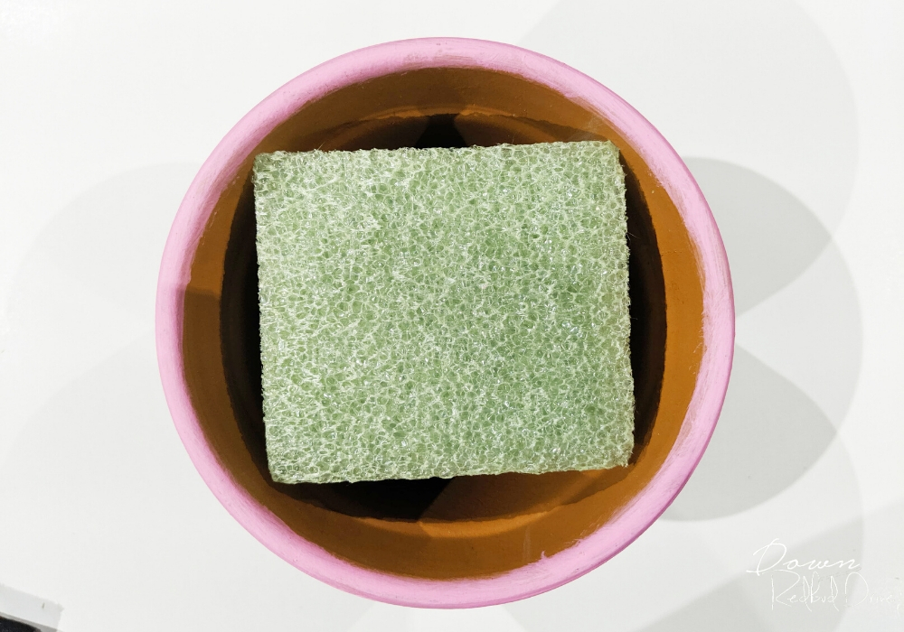 square piece of floral foam in a small pink flower pot from overhead