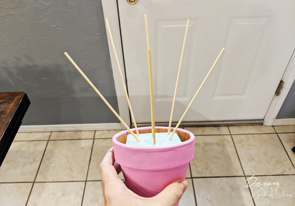 a hand holding a pink flower pot with bamboo skewers in it