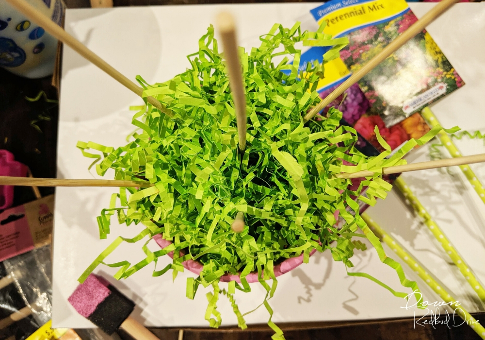 green shredded paper in a small pink flower pot with small bamboo skewers
