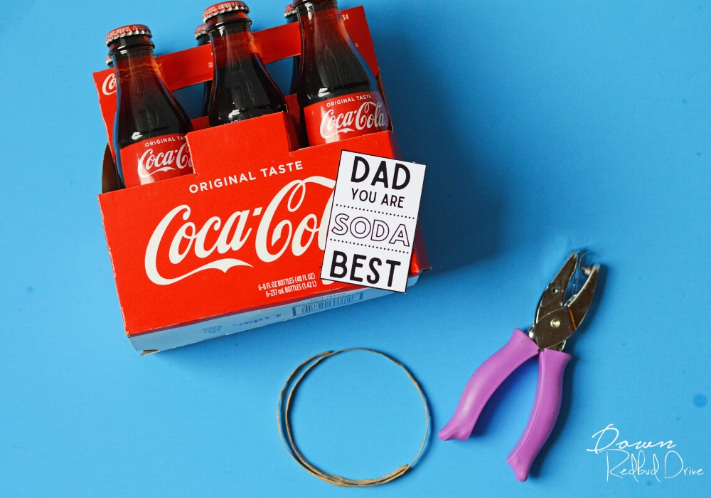 6 pack of glass coke bottles, a purple hole punch, and dad you are soda best tag, and a piece of brown raffia on a blue background
