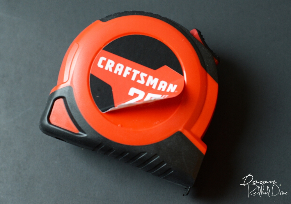 a red and black craftsman tape measure with the label peeling off on a black background