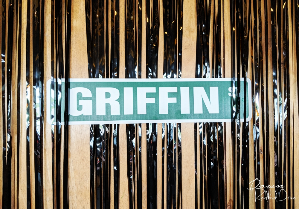 street sign on the wall that says griffin st with black streamers