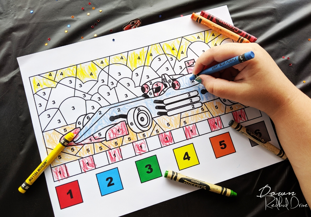 child's hand coloring a color-by-number racecar coloring sheet