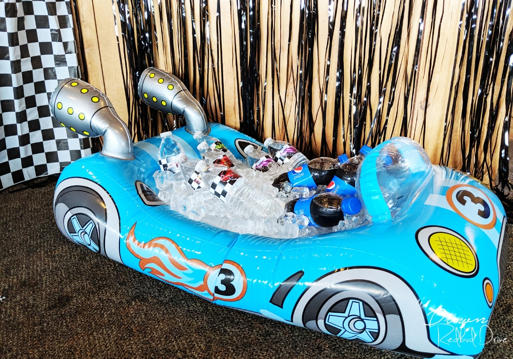 inflatable blue car on the floor with ice and water bottles in it