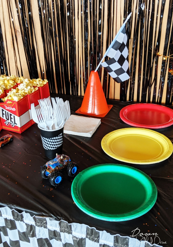 hot wheels birthday party table set up with red, green, and yellow plated, a hot wheels car, a small orange traffic cone with a checkered flag in the top of it, and white plastic forks in a black paper cup