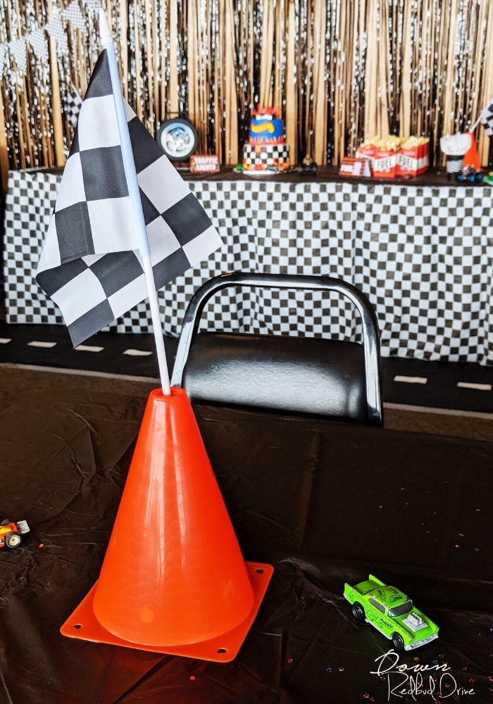 an orange tragffic cone with a black and white checkered flag stuck in the top of it sitting on a black table next to a green hot wheels car