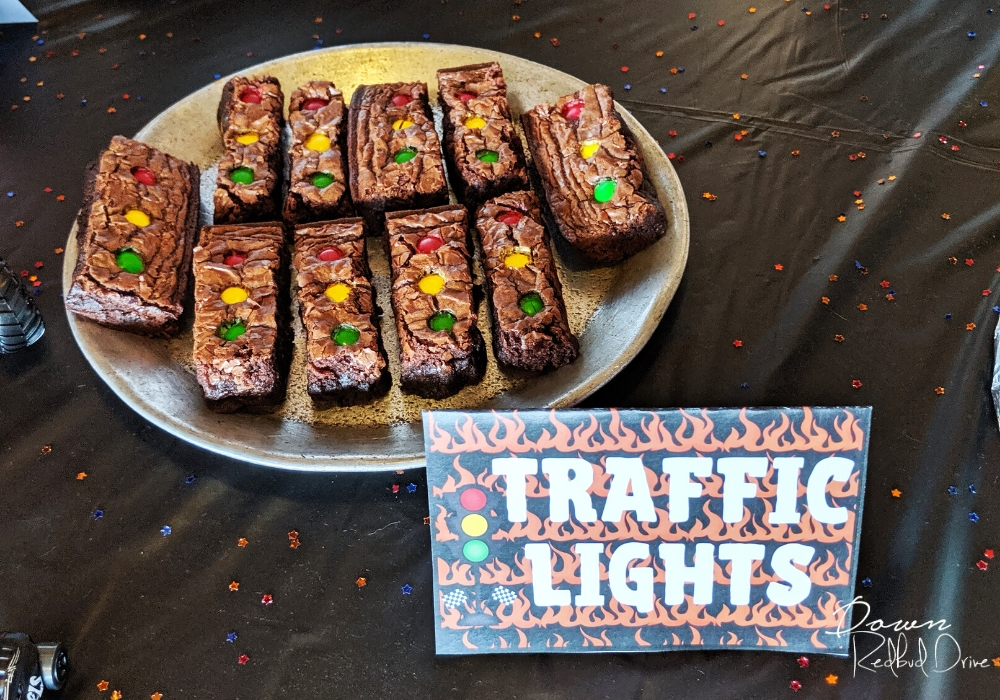 brownies cut in rectangles with red, yellow, and green M&M's on them in a line to look like a traffic light with traffic light food cards