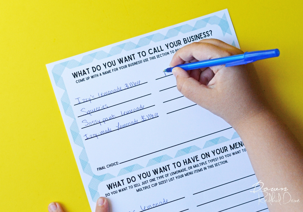 kid's hand filling out a Kid's Lemonade Stand Business Plan with a blue pen on a yellow background