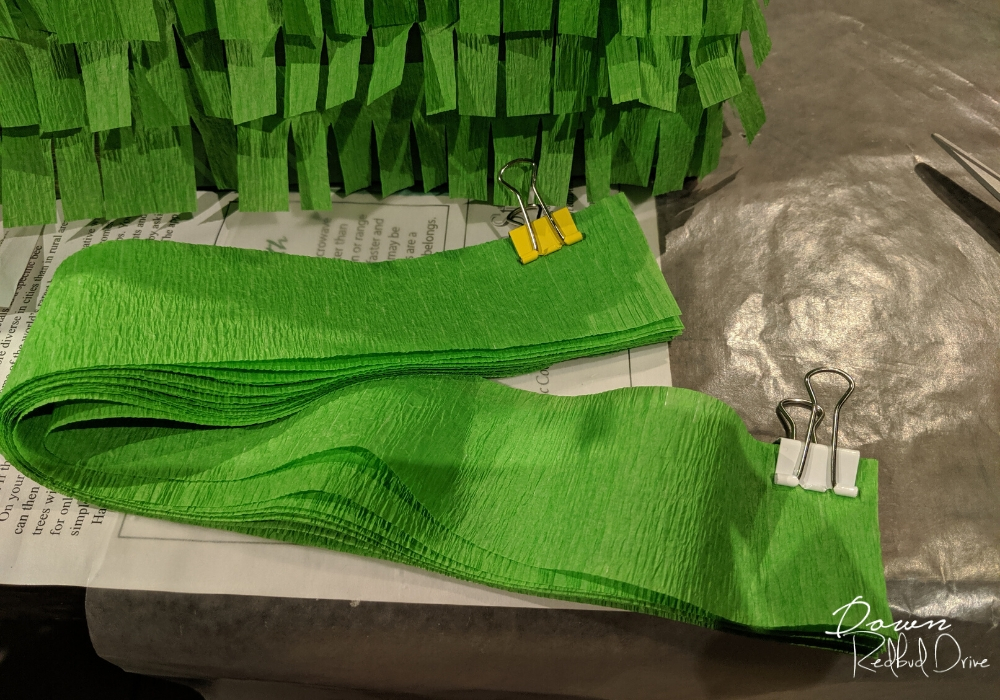 strips of green paper streamers being held together with small binder clips