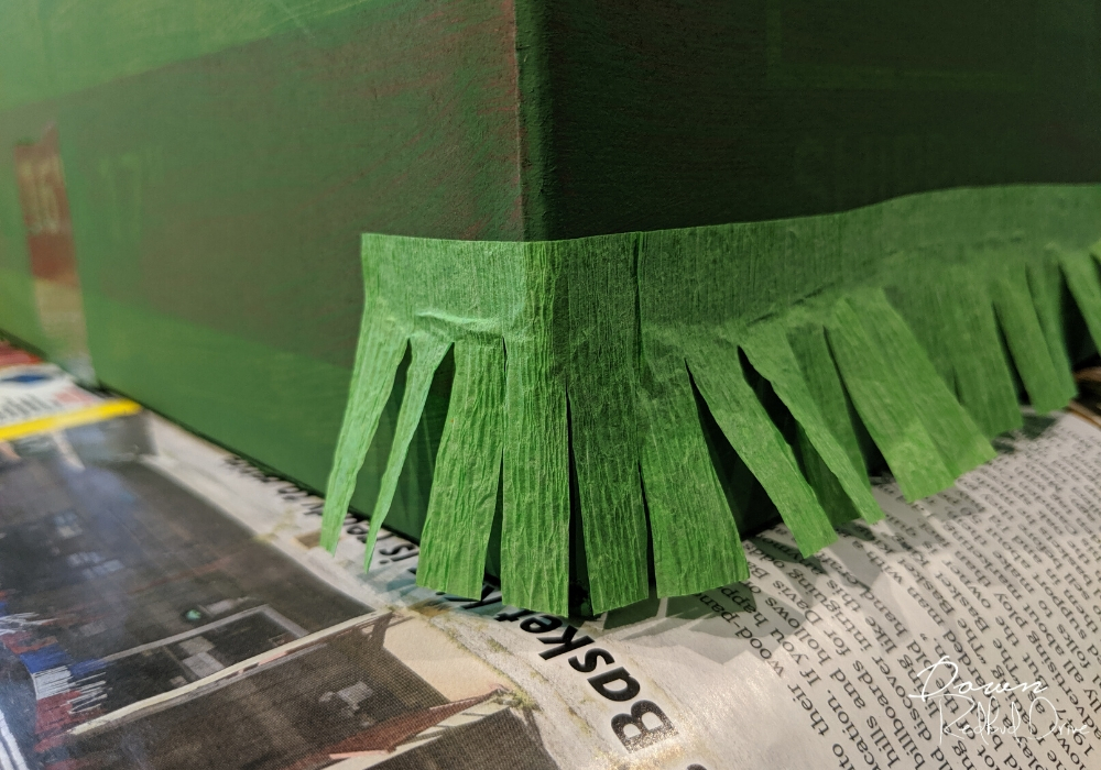 corner of a green painted box with fringer paper glued to the corner