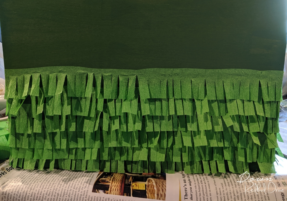 strips of green paper fringe glued to the front of a green box