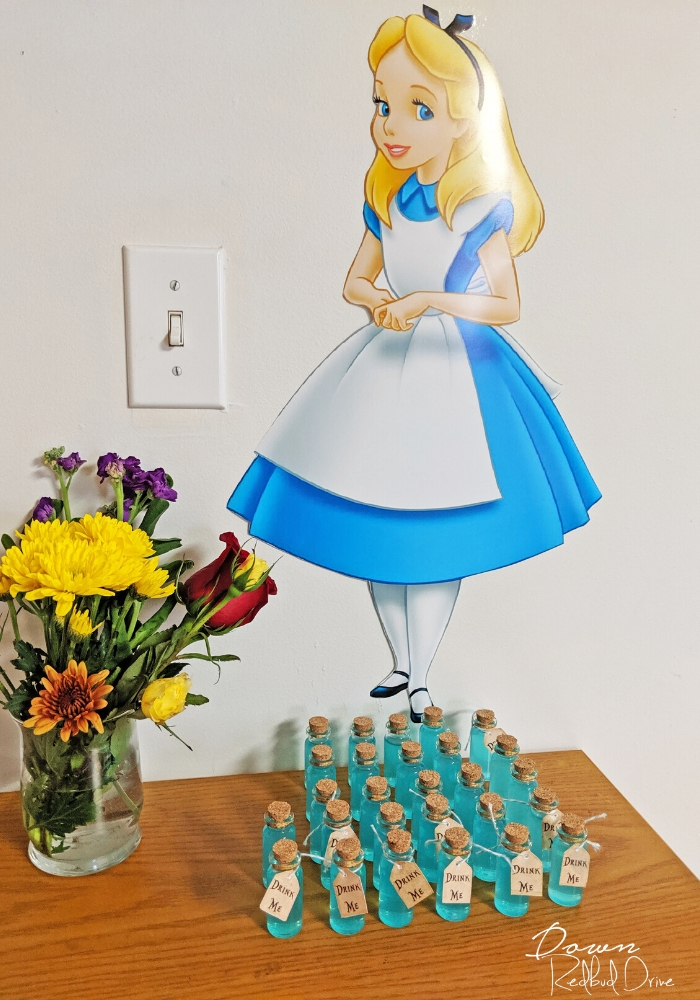 alice in wonderland wall cutout with drink me bottles on a wooden table