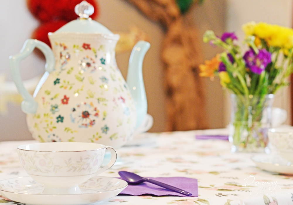 floral teapot and tea cups on a floral tablecloth