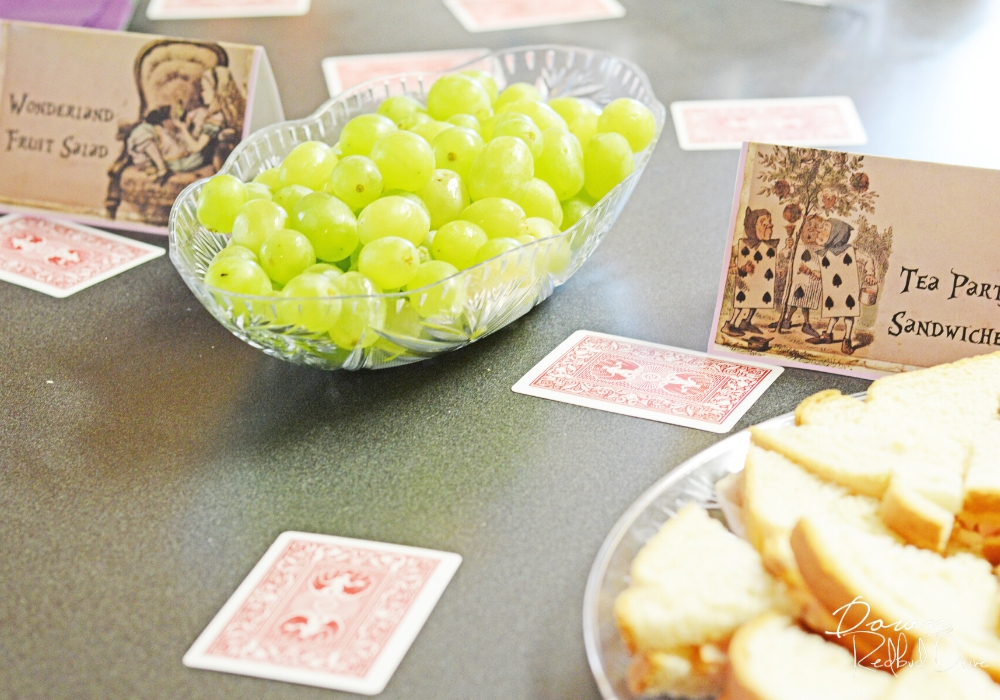 playing cards on a table at an Alice in Wonderland pbirthday party with a bowl of green grapes