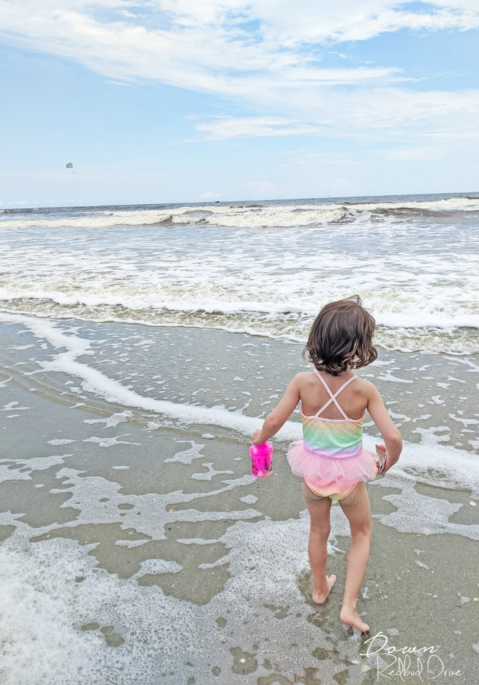 Little girl in tutu swim suit standing in the sand by the ocean at North Myrtle Beach