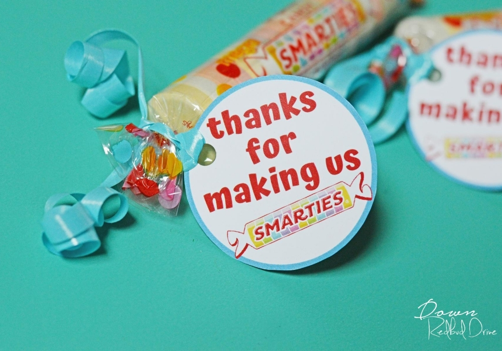 "Side shot of ""thanks for making us smarties"" tag attached to Smarties candy with a blue ribbon."