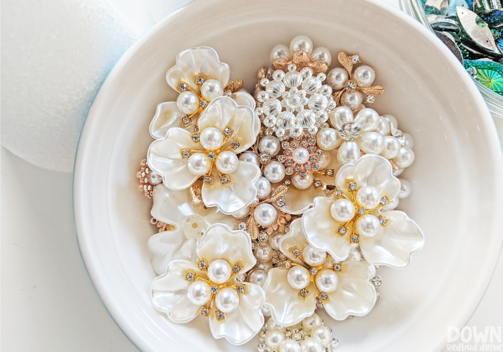 A white bowl of jewels and rhinestones.