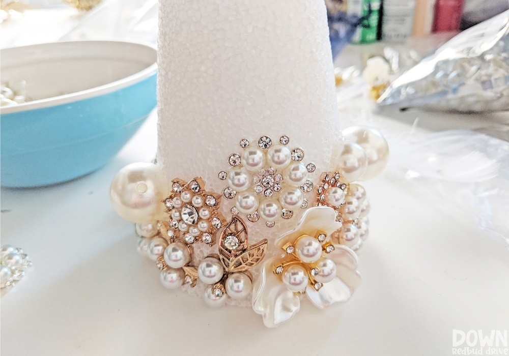 A foam cone with jewels and rhinestones glued to the bottom of it.