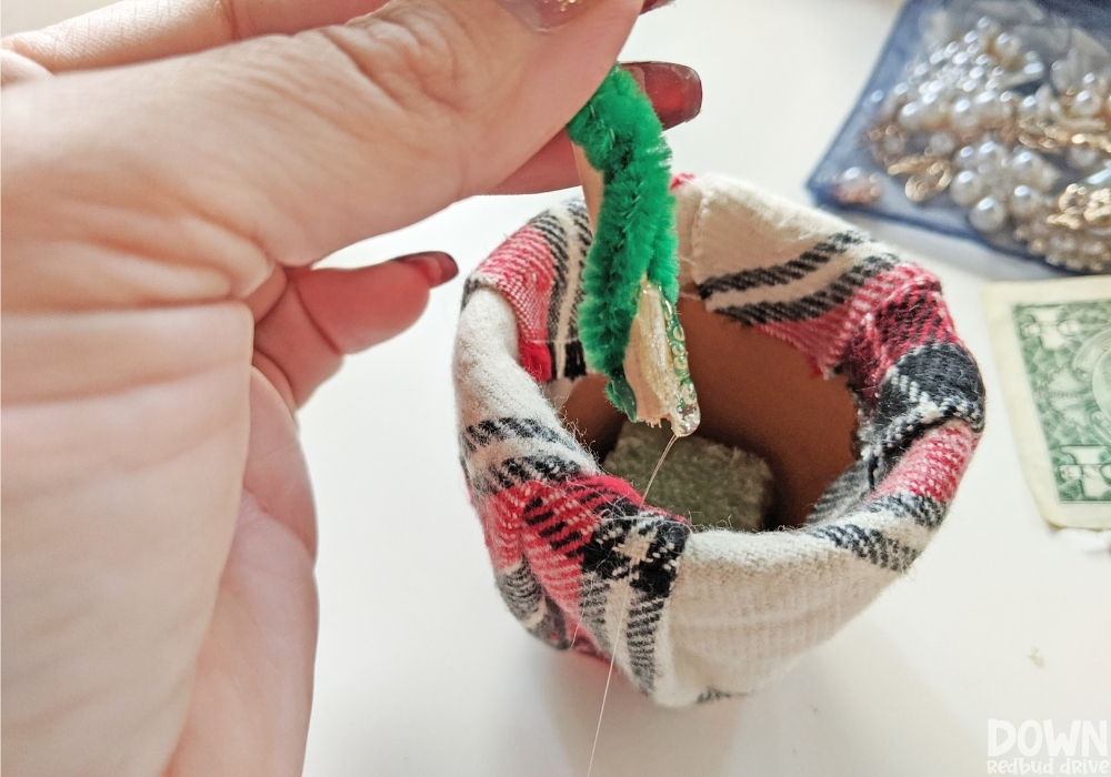 Close up of the money Christmas tree stem being glued into the pot.