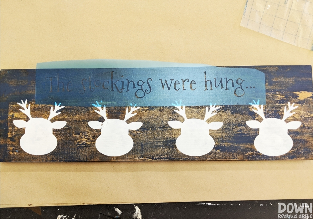 """Overhead shot of a stencil that says """"The stockings were hung..."""" applied to a wooden board with reindeer faces on it."""