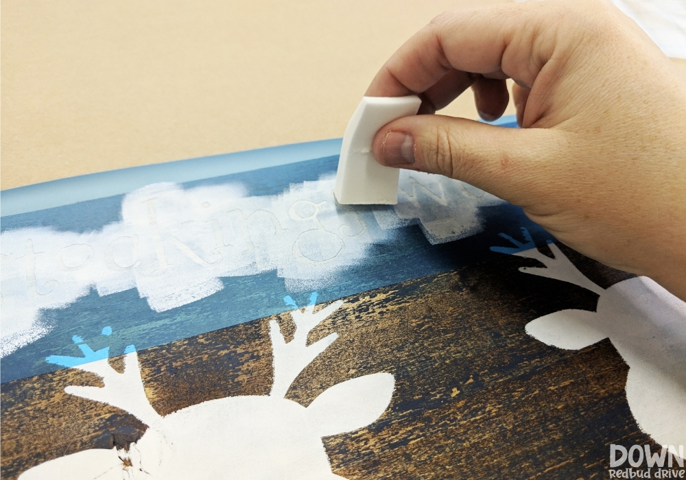 A hand painting white paint onto a stencil.