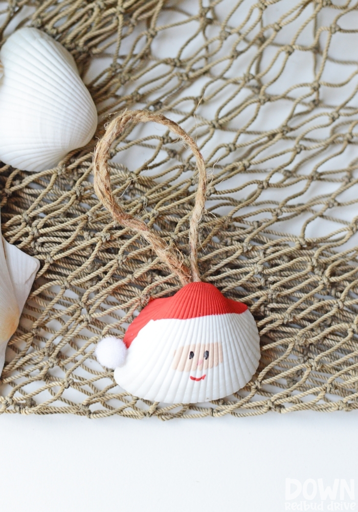 Tall picture of a Santa Seashell Ornament on a fishing net.