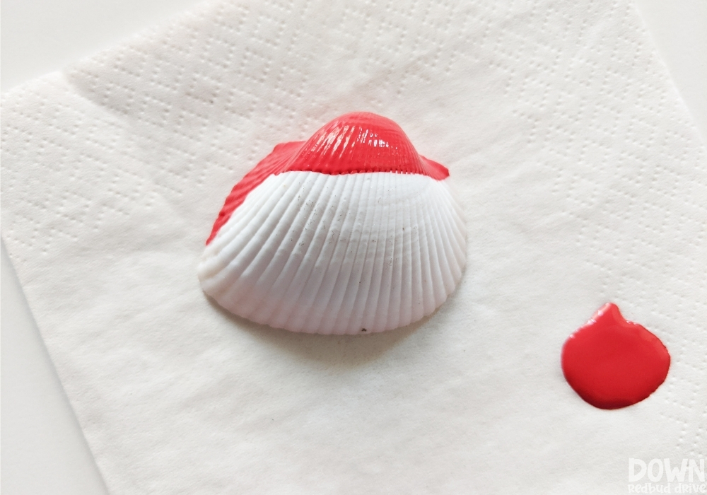 Red paint on a seashell for a Santa Christmas ornament.