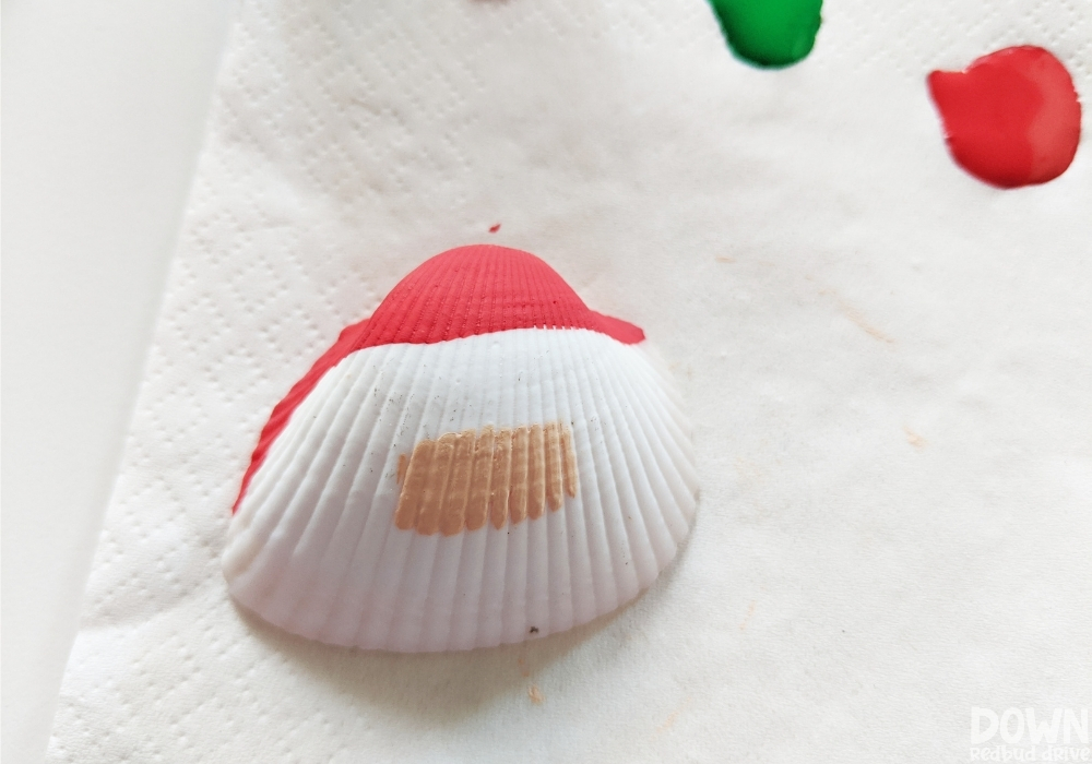Overhead shot of red and peach painted on a seashell for a Christmas ornament.