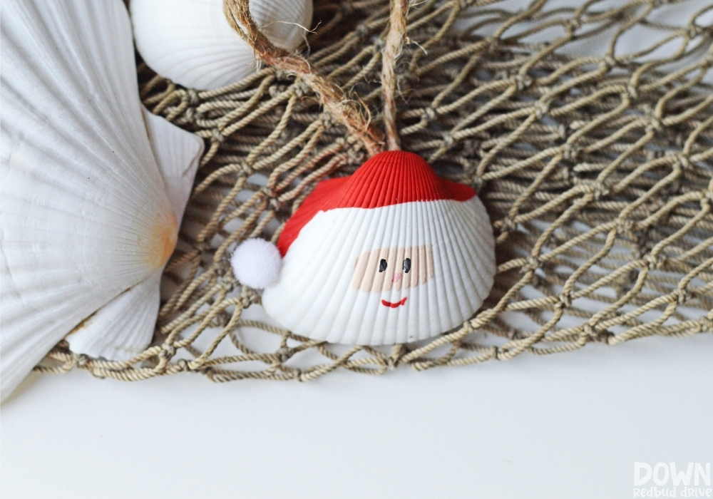 Overhead picture of the finished Santa Seashell Ornament on a fishnet next to unpainted seashells.