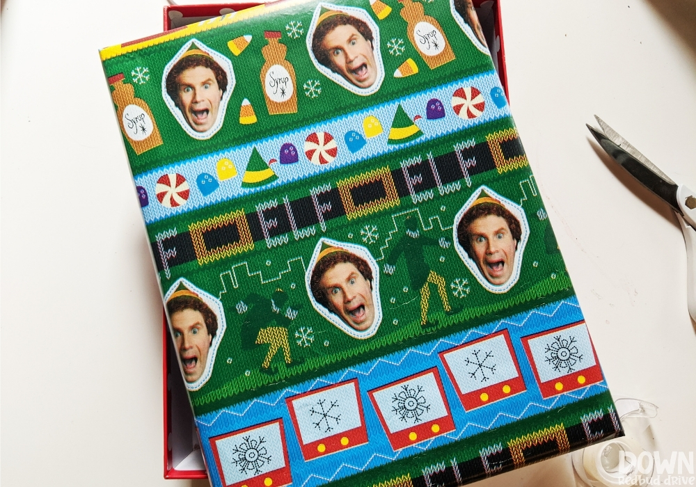 Overhead picture of a gift box wrapped in elf wrapping paper.
