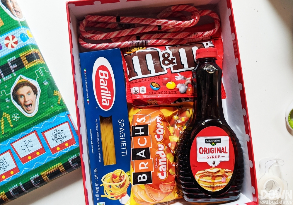 An elf decorated gift box with candy canes, peanut butter M&Ms, spaghetti, candy corn and syrup in it.