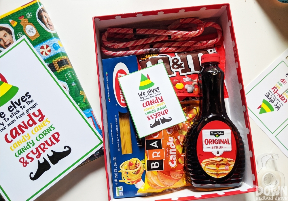 The gift box full of elf food with the printable elf card in the box.