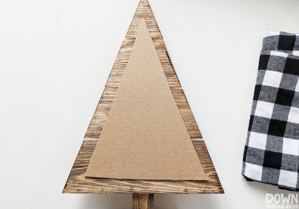The triangle cardboard cutout for the wood and fabric Christmas tree DIY sitting on top of a wooden tree decoration.