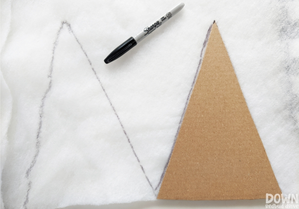 A triangle template being drawn on quilt batting to be cut.